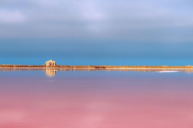 Небольшой заброшенный каменный дом стоит на розовом соленом озере под ярко-голубым небом.