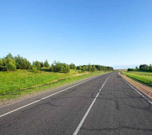 夏の小さなアスファルト道路。車道は、さまざまな方向の交通を示す白い線の道路標示で区切られています。青い空と緑の若い木トウヒ、風景の草