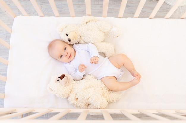 흰색 바디 수트를 입은 6 개월 된 작은 아기 소녀가 부드러운 장난감 곰과 함께 아이의 침대에 누워 있습니다.