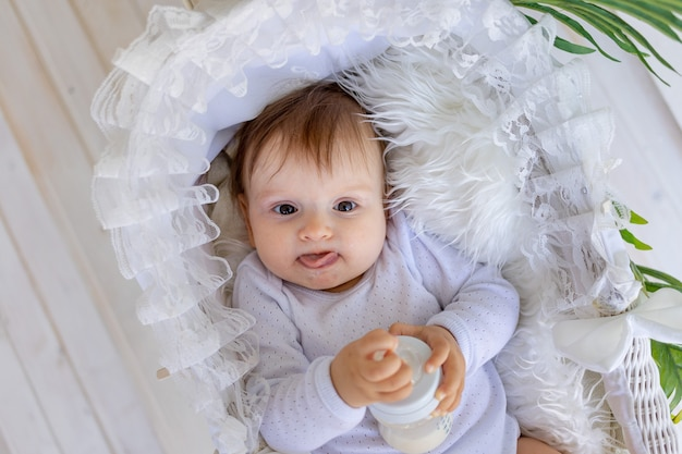 Маленькая девочка лежит в красивой колыбели в белом боди дома и держит в руках бутылку молока.