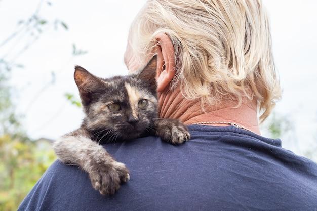 Маленький черный котенок на плече мужчины. любимые домашние животные.