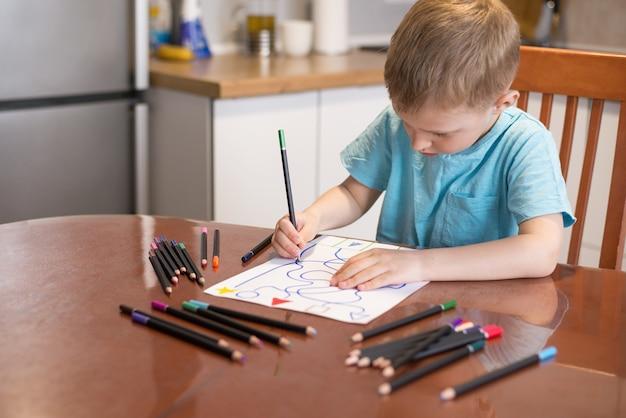 Маленький белокурый мальчик дома выполняет задание на развитие внимания и памяти нейропсихологии.
