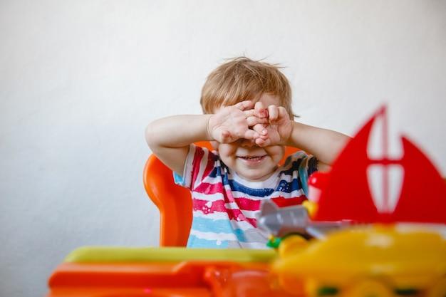 집에있는 작은 금발 소년이 플라스틱 장난감 가운데 오렌지색 어린이 테이블에 앉아 손으로 얼굴을 가리고 숨 깁니다. 고품질 사진