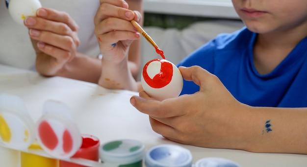 小さな金髪の少年が屋内の家庭の台所でイースター休暇のために卵を塗る