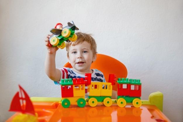 小さな金髪の少年が、明るいプラスチックのおもちゃの中で自分の机の机に座って、それを持ち上げている飛行機で遊んでいます。高品質の写真