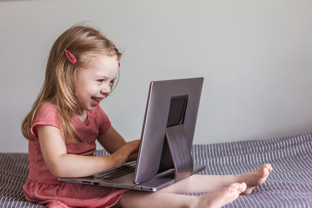 赤いドレスを着た小さなブロンドの女の子がベッドに座って、ノートパソコンの画面を見ています。オンラインコミュニケーション、ビデオコミュニケーション、教育
