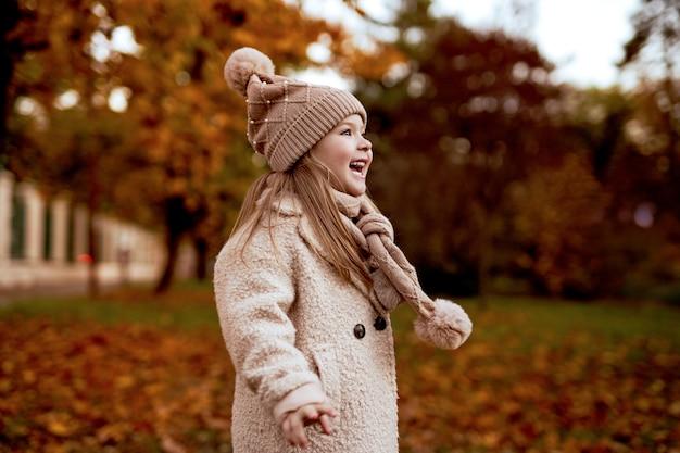 ベージュの帽子とコートとスカーフの小さな青い目のブロンドの女の子が秋の公園で笑う