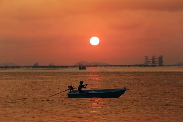 海と夕焼け空を走る小さなボート