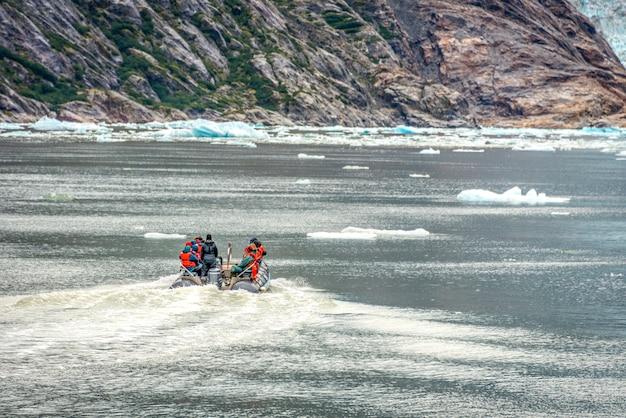アラスカの氷河への観光客のいる小さな船