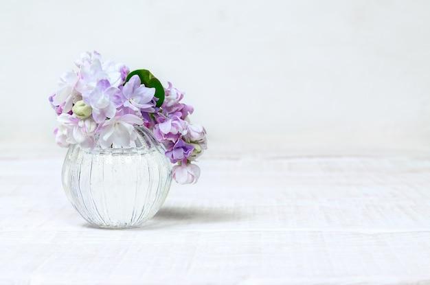 Небольшой букет цветов сирени в стеклянной вазе на белом деревянном столе