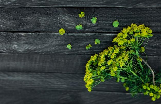 야생화의 작은 꽃다발은 밧줄로 묶여 나무 배경에 놓여
