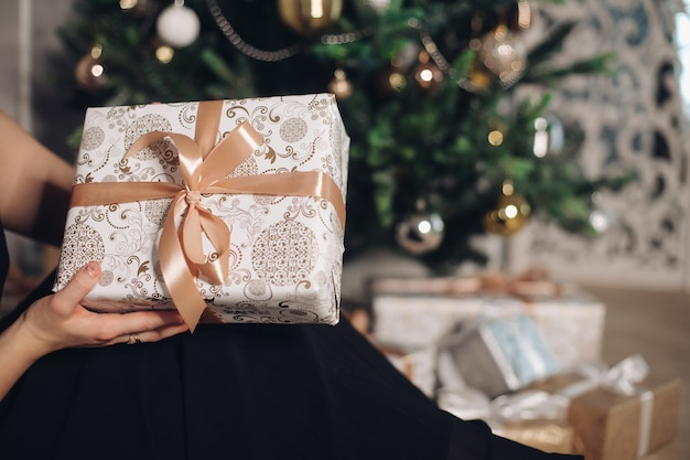 Коробочка с новогодним подарком в руке перед елкой.