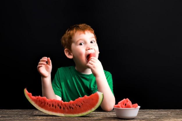작은 소년이 조각을 물고 테이블에 얇게 썬 붉은 육즙 수박 덩어리를 먹습니다.