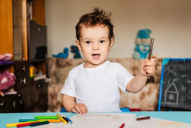 小さな男の子がテーブルの上に横たわっている紙に色鉛筆で描く