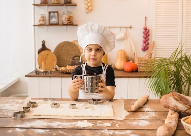 Маленький мальчик в костюме повара просеивает муку через сито на деревянной кухне