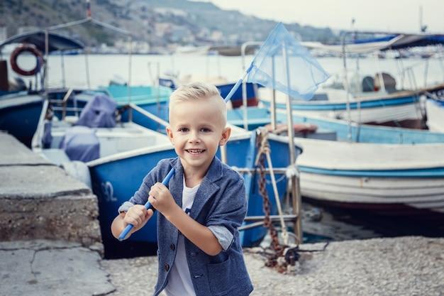 Маленький мальчик в морском стиле на фоне катеров и яхт. идея и концепция дружба, отпуск, отпуск, семья