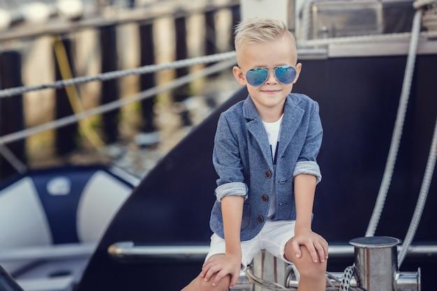 Маленький мальчик в морском стиле на фоне катеров и яхт.