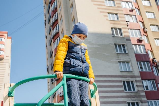 검역 기간 동안 마스크에있는 작은 소년이 놀이터에서 걷습니다. 집에있어