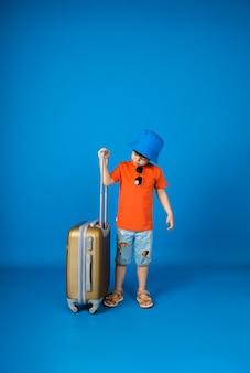 パナマ帽子をかぶった小さな男の子が、テキスト用のスペースのある青い表面にスーツケースを持って立っています