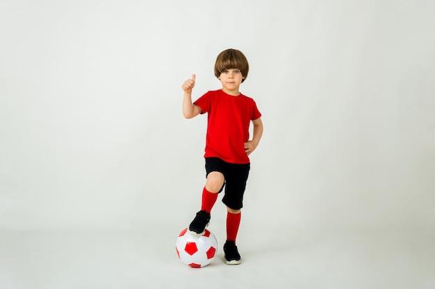 빨간 티셔츠와 반바지에 작은 소년은 텍스트를위한 공간이있는 흰색 표면에 축구 공으로 서 있습니다.