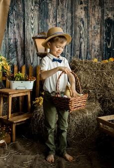 셔츠, 나비 넥타이 및 밀짚 모자에있는 작은 소년은 부활절 장식에 다채로운 계란 바구니와 함께 서 있습니다.