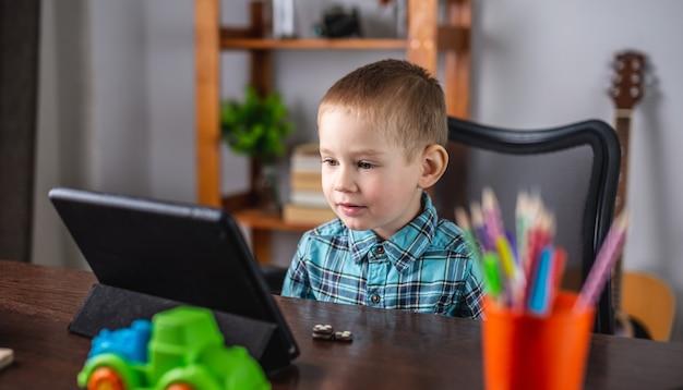 シャツを着た小さな男の子がタブレット画面を見ています