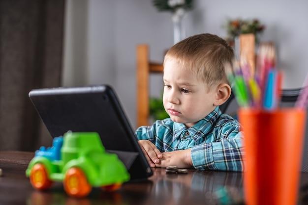 Маленький мальчик в рубашке смотрит на экран планшета
