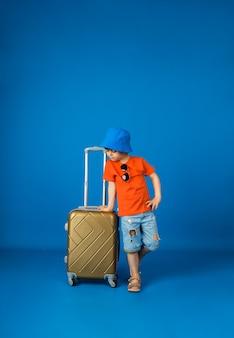 티셔츠, 반바지, 파나마 모자에 작은 소년이 텍스트를위한 공간이있는 파란색 표면에 가방을 보유하고 있습니다.