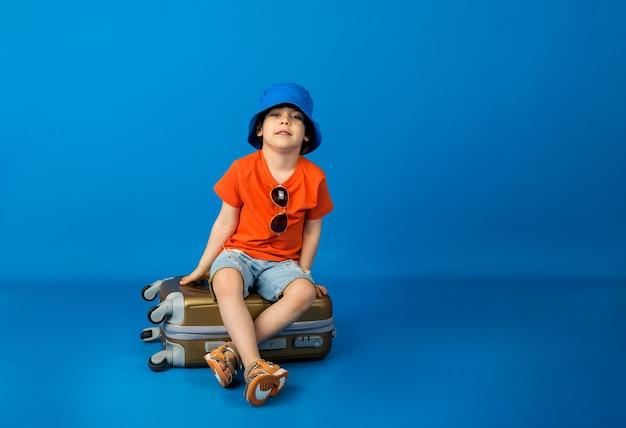 オレンジ色のtシャツとデニムのショートパンツとパナマ帽子をかぶった小さな男の子が、テキスト用のスペースがある青い表面のスーツケースに座っています。