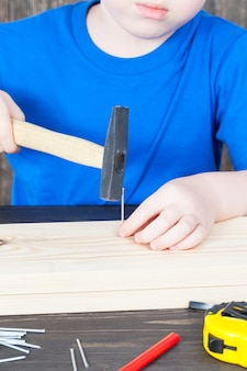 Маленький мальчик строит деревянный скворечник, вбивая в доску гвозди