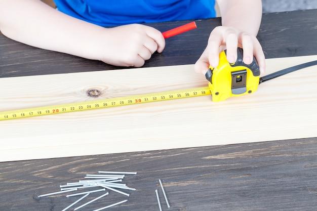 작은 소년이 나무로 된 새집을 짓고 자로 치수를 측정합니다.