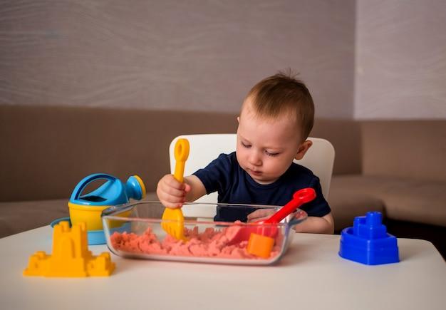 小さな男の子が部屋のテーブルで運動砂で遊んでいます