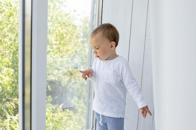 窓際に立ってママとパパを待つ小さな男の子
