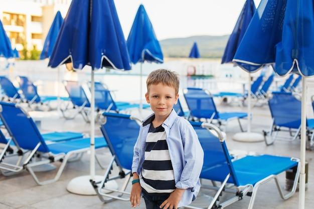 サマーリゾートのホテル敷地内にある青い傘とサンラウンジャーの間に小さな男の子が立っています。