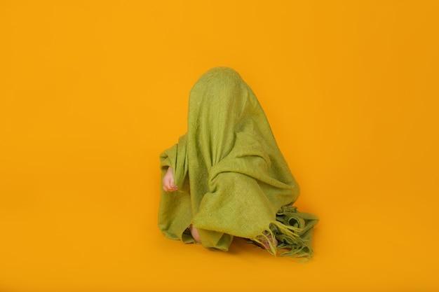 青い目の小さな男の子は、黄色の背景に座っている緑の毛布で覆われています