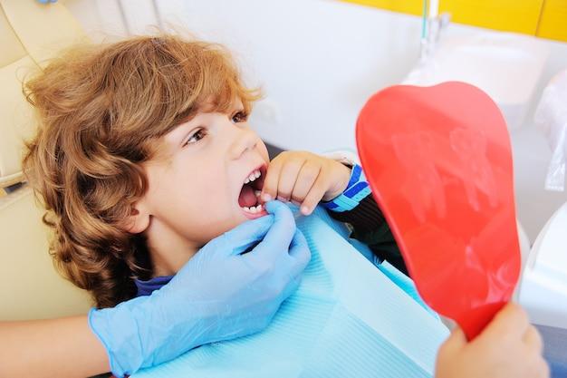 赤ちゃんの歯の1つを失った場所を示すために口を開く歯科用椅子に巻き毛の小さな男の子