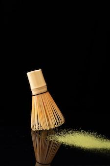 Маленькая метла подметает желтую пыль на черном