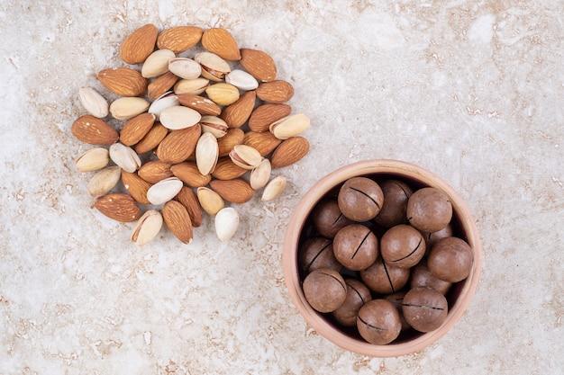 チョコレートボールのボウルの横にあるアーモンドとピスタチオの小さな束