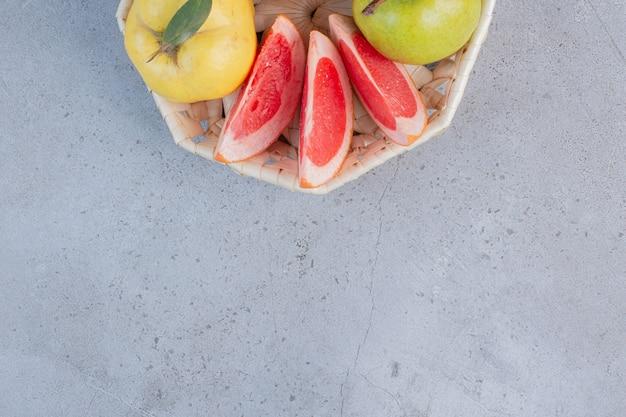 Небольшая пачка фруктов в белой корзине на мраморном фоне.