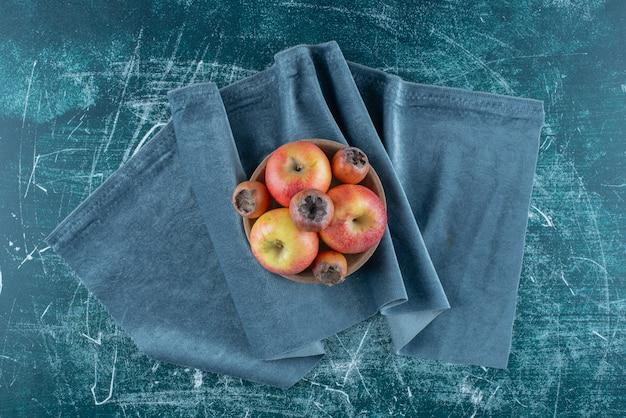 Небольшой пучок фруктов и яблок мушмулы в миске, на полотенце, на синем фоне. фото высокого качества