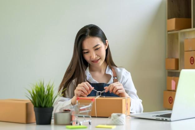 中小企業の経営者である美しい女性が、自宅の顧客に配達するための小包箱を準備しています。