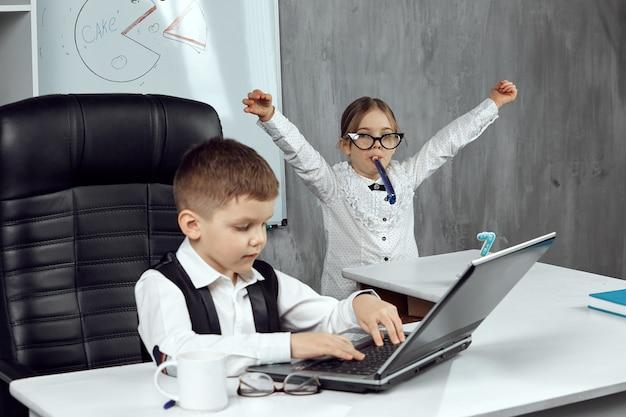 Маленькая бизнесвумен поздравляет коллегу с праздником, трубит в праздничный рог. концепция праздника на работе. дети - хозяева.