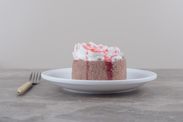 대리석 접시에 크림과 딸기 시럽을 얹은 작은 케이크