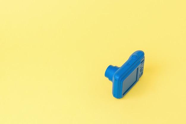 明るい黄色の背景に小さなカメラ。写真やビデオ撮影のためのスタイリッシュな機器。