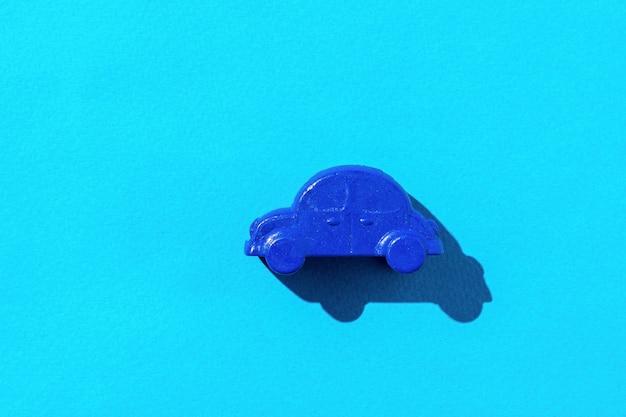 青い背景の小さな車のモデル。車の売買の概念。