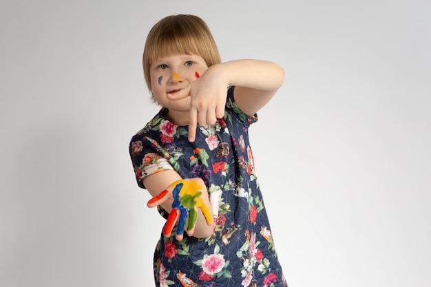 Маленькая веселая улыбающаяся девушка показывает указательным пальцем левой руки, что она испачкалась краской
