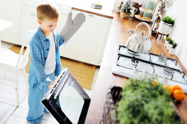 작은 아이가 장갑이 달린 파란색 잠옷을 입은 소년은 열린 오븐의 배경에 대해 서고 부엌의 배경에 대해 미소 짓습니다.