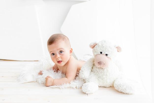 Маленький ребенок девочка 6 месяцев лежит с мягким мишкой в светлой квартире в пеленках.