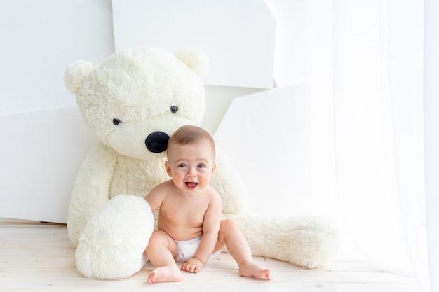 Маленький ребенок девочка 6 месяцев сидит с большим мягким медведем в светлой квартире в пеленках