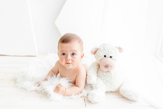 6 개월의 소녀가 작은 아이가 기저귀에 밝은 아파트에서 큰 부드러운 곰과 함께 앉아있다